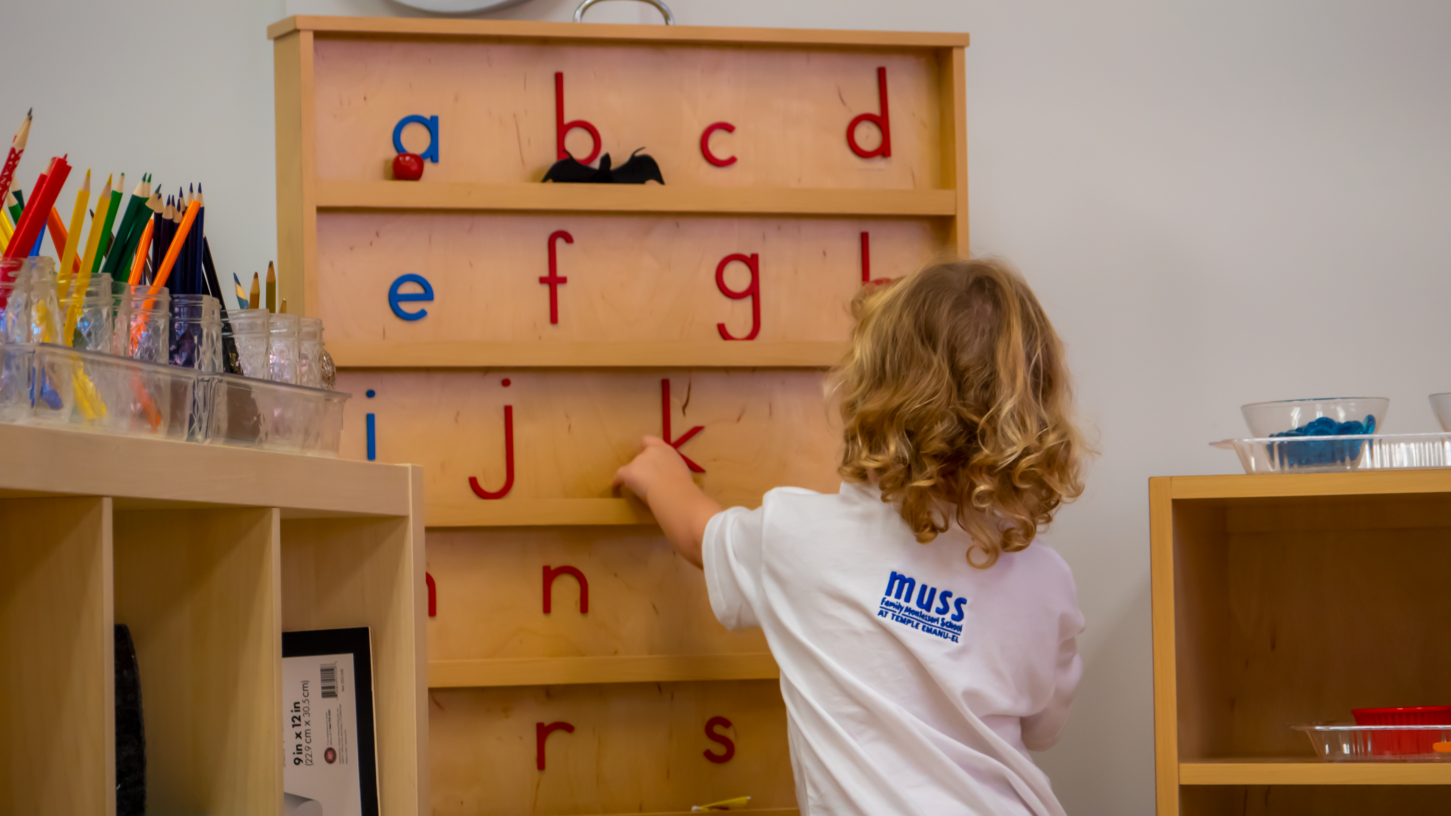 Muss student learning a montessori lesson on the alphabet