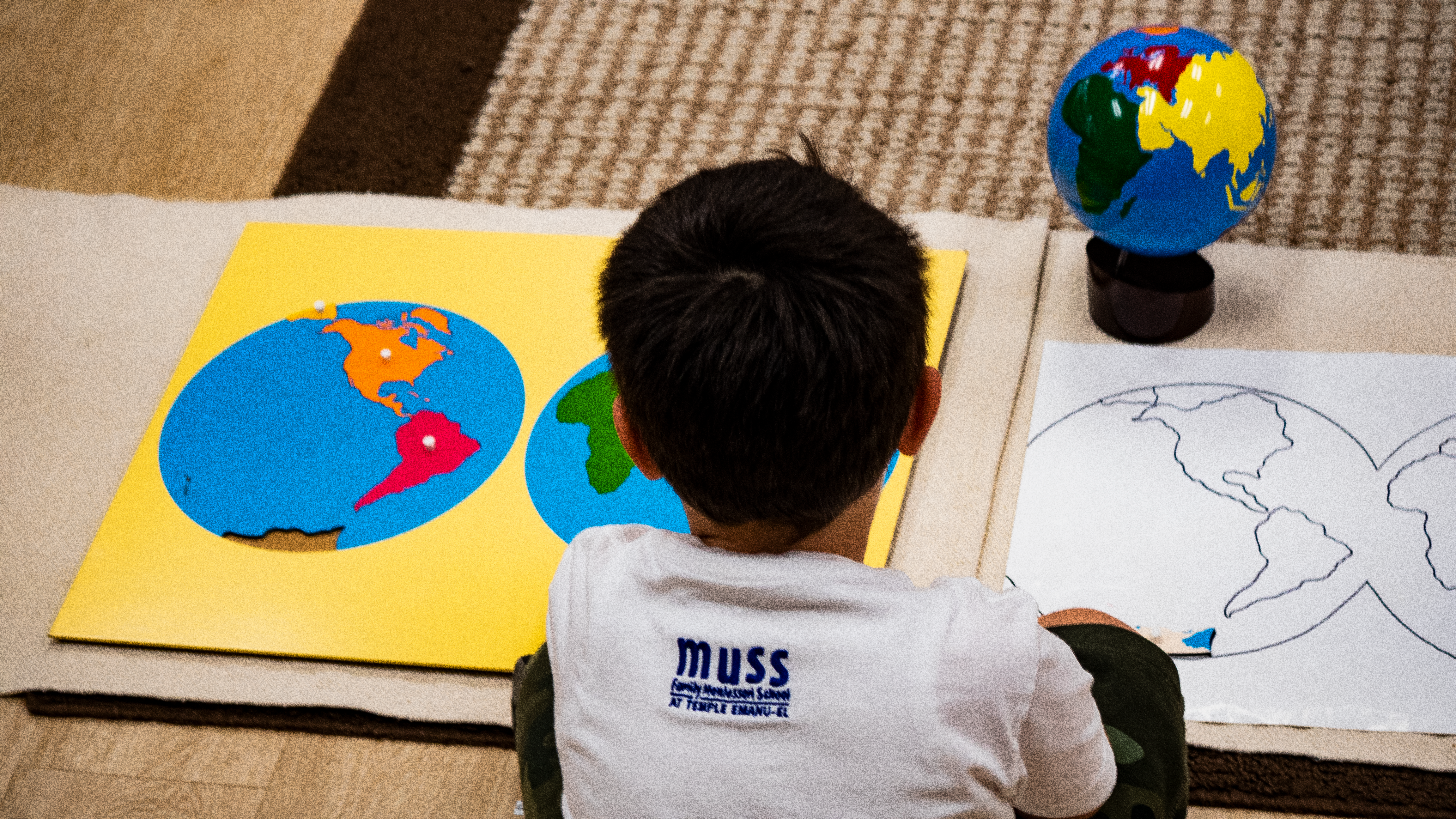 montessori student learns about the world map in a lesson at Muss Montessori at Temple Emanu-El
